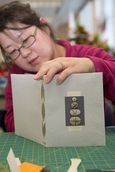 """Stehpanie Strandberg works on her project in a custom book binding workshop offered by UAF Summer Sessions during Wintermester 2013.  <div class=""""ss-paypal-button"""">Filename: AAR-13-3706-5.jpg</div><div class=""""ss-paypal-button-end"""" style=""""""""></div>"""