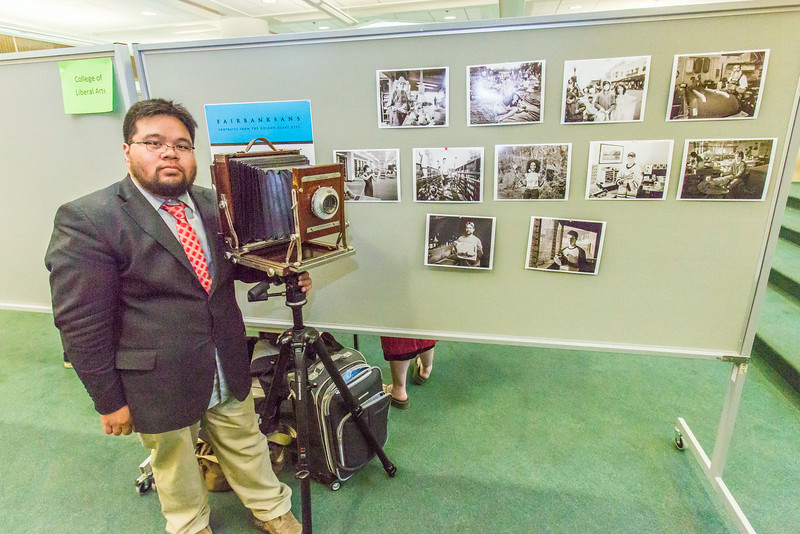 "Journalism major JR Ancheta stands with his camera in front of some of his portraits during UAF's Research Day Poster Session in Wood Center.  <div class=""ss-paypal-button"">Filename: AAR-14-4169-15.jpg</div><div class=""ss-paypal-button-end""></div>"