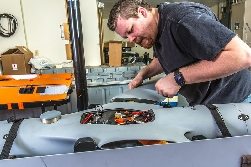 "Technician Michael Cook works on one of the unmanned aerial vehicles in UAF's Alaska Center for Unmanned Aircraft Systems Integration (ACUASI) shop in south Fairbanks.  <div class=""ss-paypal-button"">Filename: AAR-13-4026-134.jpg</div><div class=""ss-paypal-button-end""></div>"