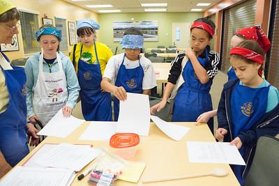 Café Tween students receive their recipes before cooking Indian cuisine.  Filename: AAR-12-3434-4.jpg