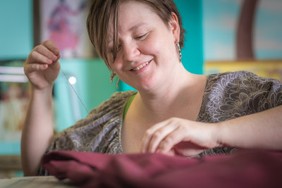Student employee and theatre major Stephanie Sandberg enjoys sewing as part of her job in the costume shop at Theatre UAF.  Filename: AAR-14-4104-32.jpg