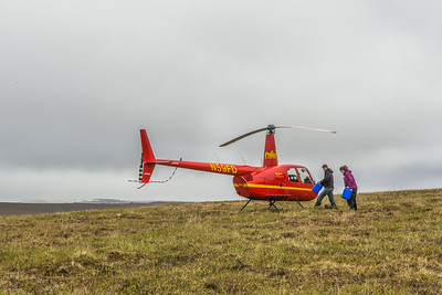 Ph.D candidate Ludda Ludwig, right, helps load a helicopter before a short flight to the Toolik Field Station from her research site near the headwaters of the Kuparuk River. Ludwig's study is focused on the movement of water and nutrients from Arctic hillslopes to streams. The Toolik research facility, located about 370 miles north of Fairbanks on Alaska's North Slope, is operated by UAF's Institute of Arctic Biology.  Filename: AAR-14-4217-123.jpg