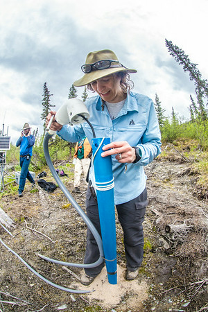 Associate professor Margaret Darrow, inspects a tube which extends deep into one of several frozen debris lobes which have appeared along the Dietrich River valley in the southern Brooks Range. Darrow, along with state geologists Ronald Daanen, left, and Trent Hubbard, are trying to figure out how to slow down or stop the movement of the lobes which threaten the Dalton Highway and the nearby trans-Alaska pipeline.  Filename: AAR-14-4214-490.jpg