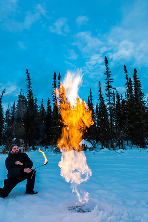Research Associate Professor Katey Walter Anthony and a research assistant set fire to escaping methane gas trapped beneath the ice on a pond on the UAF campus. The naturally occurring phenomenon is made worse by thawing permafrost and increased plant decay caused by global warming.  Filename: AAR-16-4815-04.jpg