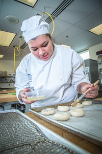 Charlotte Gordon applies an egg wash to mini-bagels served during lunch at CTC's culinary arts kitchen in the Hutchison Center.  Filename: AAR-13-3811-113.jpg