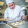 "Charlotte Gordon applies an egg wash to mini-bagels served during lunch at CTC's culinary arts kitchen in the Hutchison Center.  <div class=""ss-paypal-button"">Filename: AAR-13-3811-113.jpg</div><div class=""ss-paypal-button-end"" style=""""></div>"