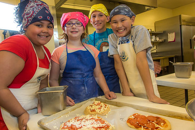 Local school kids made their own pizzas while attending the UAF Summer Sessions Baking Blitz May 28 in the Hutchison kitchen.  Filename: AAR-14-4203-17.jpg