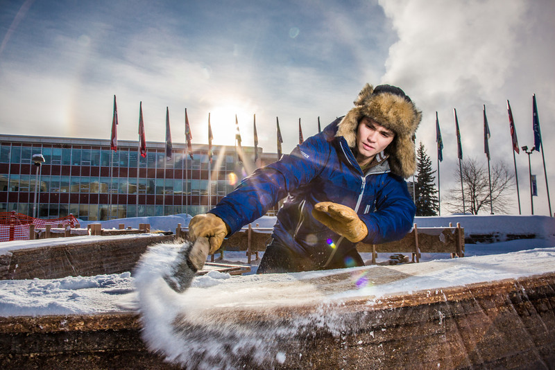 "Engineering major Ryan Williams-Cudo, project leader of the traditional ice arch project, brushes the previous night's snowfall off the main structure. Cudo and other student engineers designed and built the 2013 ice arch using a combination of water and sawdust to end up with a substance many times stronger than concrete.  <div class=""ss-paypal-button"">Filename: AAR-13-3733-22.jpg</div><div class=""ss-paypal-button-end"" style=""""></div>"