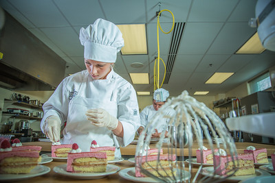 Stephanie Valentik applies fresh berries to a batch of raspberry tarts being served during lunch at CTC's culinary arts kitchen in the Hutchison Center.  Filename: AAR-13-3811-162.jpg
