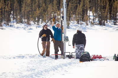 Associate Professor Mat Wooller, blue shirt, and Ph.D. candidate Jim Shobe, left, test a new vibra-coring system through a hole in lake ice to sample long cores of sediment deep below the lake's bottom. Also helping is Terry Smith, right, a North Pole High School student intern.  Filename: AAR-12-3346-026.jpg