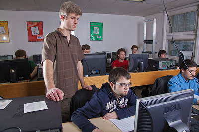 Faculty member John Quan looks over the shoulder of one of his students in the Chapman Building ASSERT lab.  Filename: AAR-12-3272-17.jpg