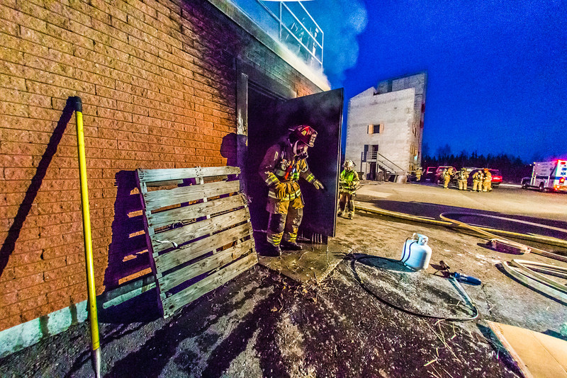 "UFD Captain Ben Fleagle exits a burning building during a live training drill at the Fairbanks Fire Training Center in South Fairbanks. McClean was helping lead the session with about 30 students participating  department's Tuesday night drill Oct. 22.  <div class=""ss-paypal-button"">Filename: AAR-13-3978-160.jpg</div><div class=""ss-paypal-button-end"" style=""""></div>"