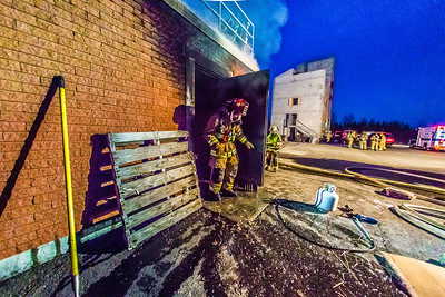 UFD Captain Ben Fleagle exits a burning building during a live training drill at the Fairbanks Fire Training Center in South Fairbanks. McClean was helping lead the session with about 30 students participating  department's Tuesday night drill Oct. 22.  Filename: AAR-13-3978-160.jpg