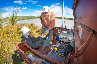 Paul Duvoy, left, and Jack Schmid, research professionals with the Alaska Center for Energy and Power, test the battery installed at a remote recording station set up on the banks of the Tanana River near Nenana. The pair are part of a team conducting research on the feasibility of using the river current to generate electricity for potential use throughout rural Alaska.  Filename: AAR-12-3500-169.jpg