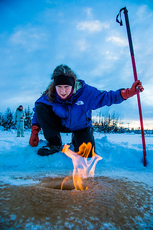 Research Associate Professor Katey Walter Anthony inspects flaming methane gas seeping from a hole in the ice on the surface of a pond on the UAF campus. The naturally occurring phenomenon is made worse by thawing permafrost and increased plant decay caused by global warming.  Filename: AAR-16-4815-20.jpg