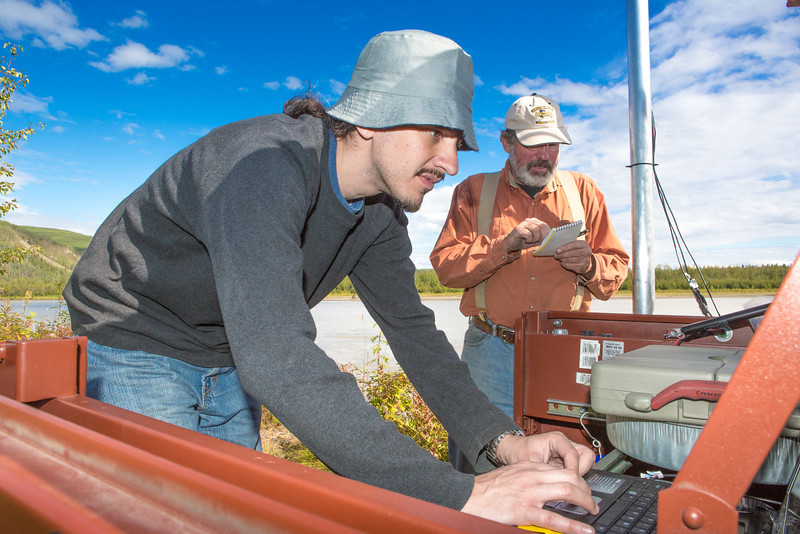 """Paul Duvoy, front, and Jack Schmid, research professionals with the Alaska Center for Energy and Power, enter data into a remote recording station set up on the banks of the Tanana River near Nenana. The pair are part of a team conducting research on the feasibility of using the river current to generate electricity for potential use throughout rural Alaska.  <div class=""""ss-paypal-button"""">Filename: AAR-12-3500-154.jpg</div><div class=""""ss-paypal-button-end"""" style=""""""""></div>"""