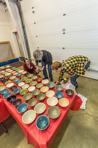 UAF art major Ian Wilkinson, at right, helps volunteers lay out 1,200 individual bowls he made on tables at the Fairbanks Community Food Bank. The bowls were sold as part of his senior thesis project, helping to raise about $18,000 he donated to the local charity.  Filename: AAR-13-3790-7.jpg