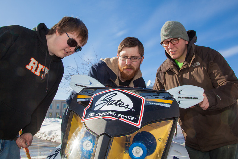 """Clean Snowmachine team members Ben Neubauer, left, Isaac Thompson, center, and Karlin Swearingen check out their machine after it's return  to campus after taking top honors in the Society of Automotive Engineers' Clean Snowmobile Challenge in Houghton, Mich.  <div class=""""ss-paypal-button"""">Filename: AAR-12-3337-33.jpg</div><div class=""""ss-paypal-button-end"""" style=""""""""></div>"""