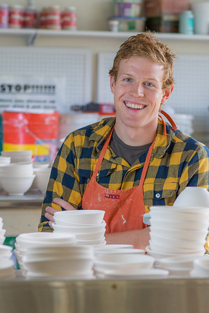 Art major Ian Wilkinson poses with a few of the approximately 1,000 ceramic bowls needed for his senior thesis project in the fine arts complex on the Fairbanks campus.  Filename: AAR-12-3547-102.jpg