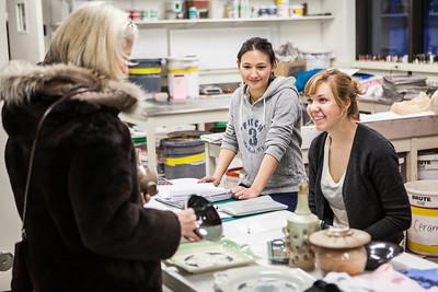 Emily Blurton, center, and Kirsten Olson, complete a transaction during the 2012 Student Artist Ceramics sale in December 2012.  Filename: AAR-12-3683-26.jpg