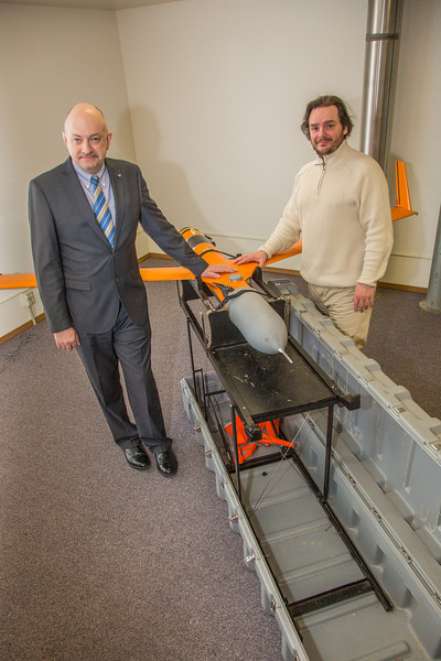 "Marty Rogers, left, chief operating officer with the Alaska Center for Unmanned Aircraft Systems Integration (ACUASI), stands with Sigurder Hrafnsson, chairman of the UAS test site and research facilities in Iceland by one of their test aircraft at the ACUASI offices in Fairbanks.  <div class=""ss-paypal-button"">Filename: AAR-14-4090-22.jpg</div><div class=""ss-paypal-button-end"" style=""""></div>"