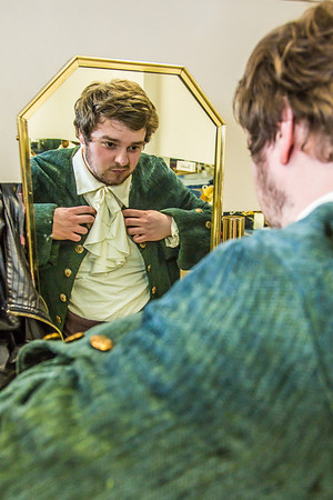 """Brian Tuohy, playing the title role in Theatre UAF's production of """"Tartuffe,"""" gets into his costume before performing a live teaser in Wood Center a couple of days before opening night.  Filename: AAR-14-4121-1.jpg"""