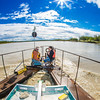 """Jack Schmid, left, and Paul Duvoy, research professionals with the Alaska Center for Energy and Power, take measurements on a prototype deployment boom on the Tanana River near Nenana. The pair are part of a team conducting research on the feasibility of using the river current to generate electricity for potential use throughout rural Alaska.  <div class=""""ss-paypal-button"""">Filename: AAR-12-3500-061.jpg</div><div class=""""ss-paypal-button-end"""" style=""""""""></div>"""