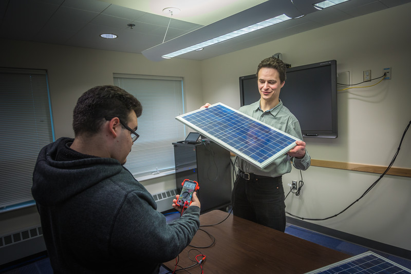 """Assistant Professor Tom Marsik, right, demonstrates how a solar panel can generate electricity from florescent lights with undergraduate Andrew Akelkok at UAF's Bristol Bay Campus in Dillingham.  <div class=""""ss-paypal-button"""">Filename: AAR-16-4860-241.jpg</div><div class=""""ss-paypal-button-end""""></div>"""