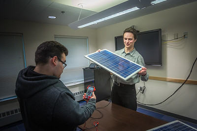 Assistant Professor Tom Marsik, right, demonstrates how a solar panel can generate electricity from florescent lights with undergraduate Andrew Akelkok at UAF's Bristol Bay Campus in Dillingham.  Filename: AAR-16-4860-241.jpg