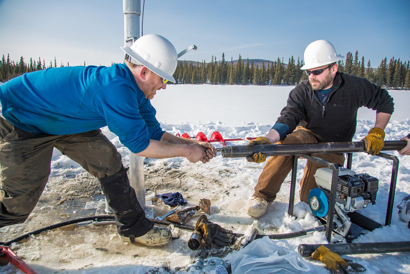 "Associate Professor Mat Wooller, blue shirt, and Ph.D. candidate Jim Shobe, right, test a new vibra-coring system through a hole in lake ice to sample long cores of sediment deep below the lake's bottom.  <div class=""ss-paypal-button"">Filename: AAR-12-3346-117.jpg</div><div class=""ss-paypal-button-end"" style=""""></div>"