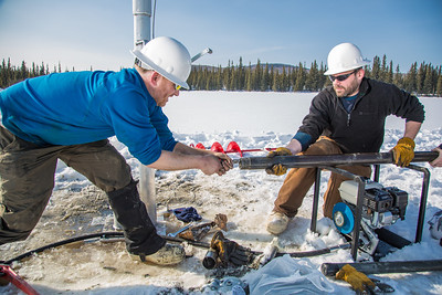 Associate Professor Mat Wooller, blue shirt, and Ph.D. candidate Jim Shobe, right, test a new vibra-coring system through a hole in lake ice to sample long cores of sediment deep below the lake's bottom.  Filename: AAR-12-3346-117.jpg