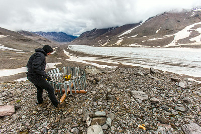 Matvey Debolskiy, a Ph.D. student in geophysics, balances a precipitation gauge on a ridge above the Jarvis Glacier in the eastern Alaska Range.  Filename: AAR-14-4256-303.jpg