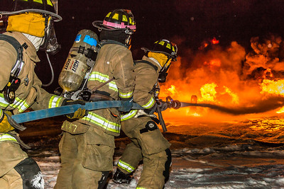 Student firefighters with the University Fire Department spray water on a blaze of burning fuel during a live training drill at the Fairbanks International Airport.  Filename: AAR-13-3995-180.jpg
