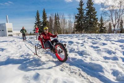 Mechanical engineering majors Daniel Sandstrom, left, Eric Bookless and Neil Gotschall, front, demonstrate their fat tire ski bike they designed and built for paraplegic users as their spring 2016 senior design project. The bike is powered by pushing and pulling on the handles.  Filename: AAR-16-4856-05.jpg