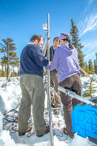 Research associate professor Javier Fochesatto, left, ACEP intern Luke George, and Daisy Huang, a research engineer for the Alaska Center for Energy and Power, set up a remote meteorological station on a hillside near the Black Rapids Lodge, about 150 miles southeast of Fairbanks. The station will record wind speed and direction, as well as temperatures at different altitudes.  Filename: AAR-13-3843-147.jpg