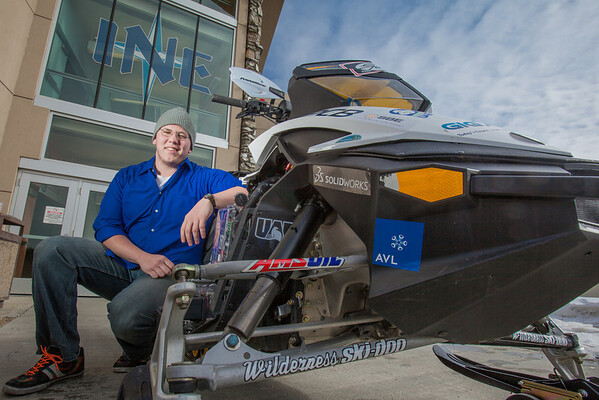 """Mechanical enineering major Karlin Swearingen poses with the UAF team's snowmobile in front of the Duckering Building after its return from competing in the Society of Automotive Engineers' Clean Snowmobile Challenge in Houghton, Mich.  <div class=""""ss-paypal-button"""">Filename: AAR-12-3345-097.jpg</div><div class=""""ss-paypal-button-end"""" style=""""""""></div>"""