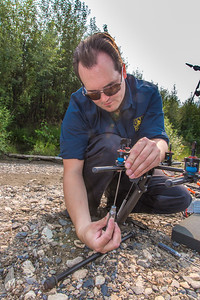 Trevor Parcell with the Alaska Center for Unmanned Aircraft Systems Integration (ACUASI) sets up a piloting station on a gravel bar along the upper Chena River. The UAV pilot was taking part in a joint effort with the U.S. Fish and Wildlife Service to collect video of important king salmon spawning habitat.  Filename: AAR-15-4593-149.jpg