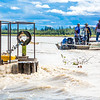 "Researchers with UAF's School of Fisheries and Ocean Sciences and the Alaska Center for Energy and Power (ACEP) watch as debris hits a prototype deployment boom on a barge anchored in the Tanana River near Nenana. They're part of a team conducting research on the feasibility of using the river current to generate electricity for potential use throughout rural Alaska.  <div class=""ss-paypal-button"">Filename: AAR-12-3500-133.jpg</div><div class=""ss-paypal-button-end"" style=""""></div>"