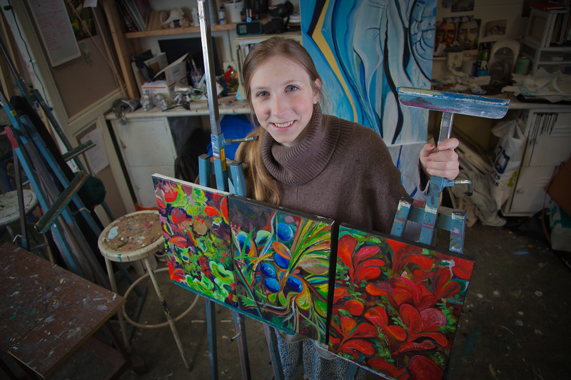 """Art major Klara Maisch poses with some of her paintings in the Fine Arts studio.  <div class=""""ss-paypal-button"""">Filename: AAR-12-3299-57.jpg</div><div class=""""ss-paypal-button-end"""" style=""""""""></div>"""