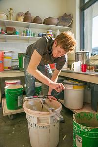 Art major Ian Wilkinson mixes glaze in the UAF ceramics studio.  Filename: AAR-13-3752-5.jpg
