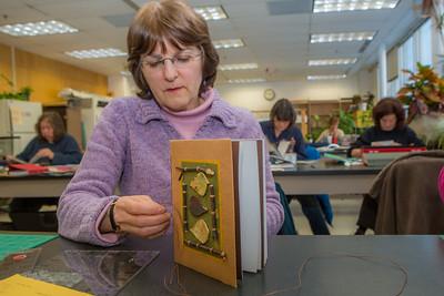 Barbara Travis works on her project in a custom book binding workshop offered by UAF Summer Sessions during Wintermester 2013.  Filename: AAR-13-3706-2.jpg