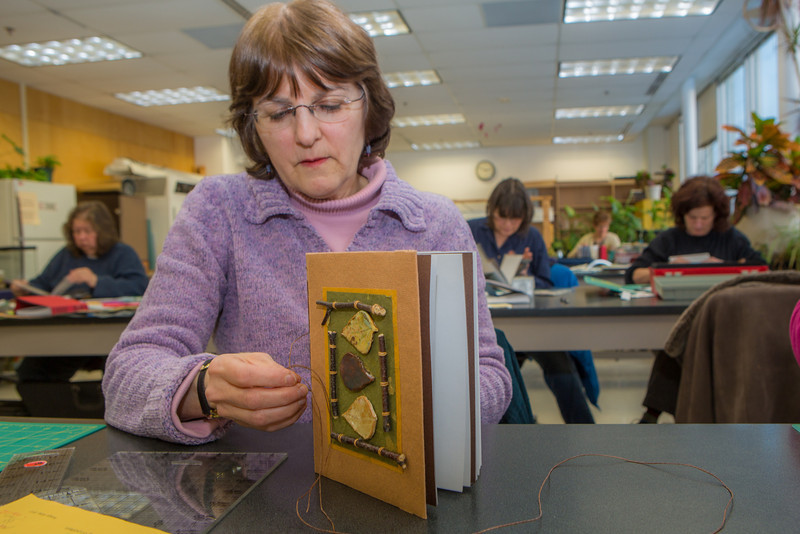 "Barbara Travis works on her project in a custom book binding workshop offered by UAF Summer Sessions during Wintermester 2013.  <div class=""ss-paypal-button"">Filename: AAR-13-3706-2.jpg</div><div class=""ss-paypal-button-end"" style=""""></div>"