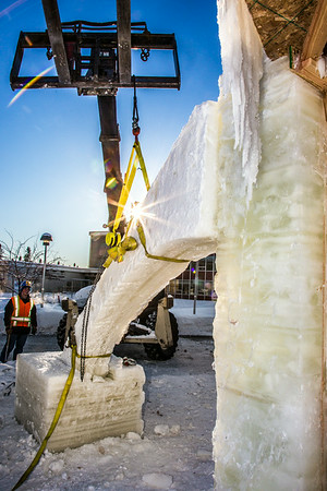 Volunteers from GHEMM, Inc. use a crane to lift the buttresses for this year's student-built ice arch into position in Cornerstone Plaza on campus. The annual ice arch is designed and built by a team of engineering students, a UAF tradition going back more than 60 years.  Filename: AAR-14-4078-19.jpg
