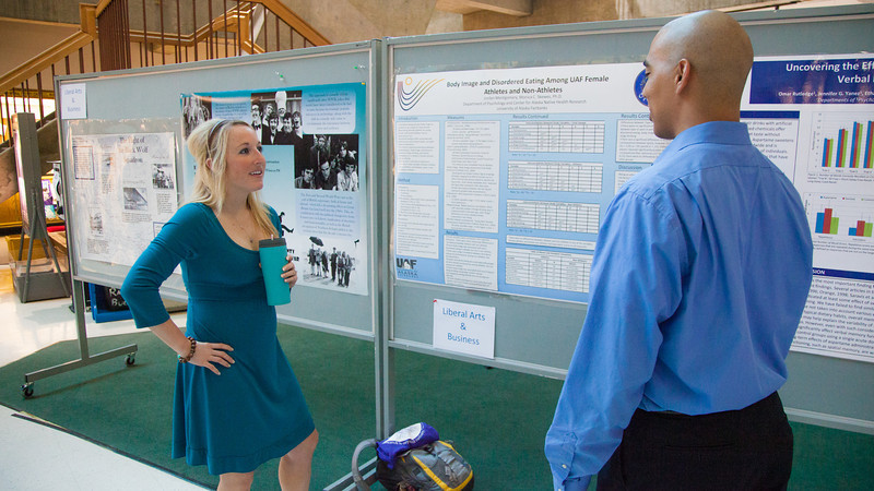 """Psychology major Jordyn Montgomery discusses results of her research project on body image and eating disorders with a colleague during the Research Day poster session in the Wood Center.  <div class=""""ss-paypal-button"""">Filename: AAR-12-3363-02.jpg</div><div class=""""ss-paypal-button-end"""" style=""""""""></div>"""
