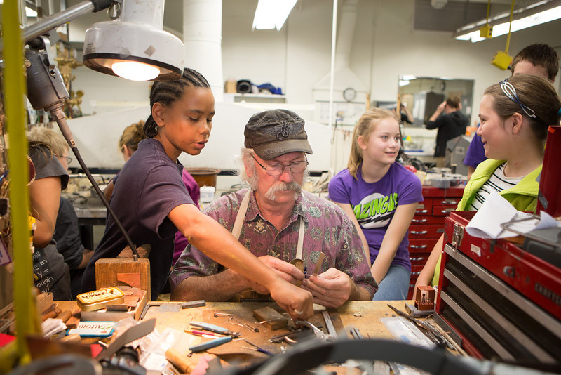 """Eli Evans, 11, reaches for a tool at metals class during UAF's Visual Arts Academy.  <div class=""""ss-paypal-button"""">Filename: AAR-12-3427-24.jpg</div><div class=""""ss-paypal-button-end"""" style=""""""""></div>"""