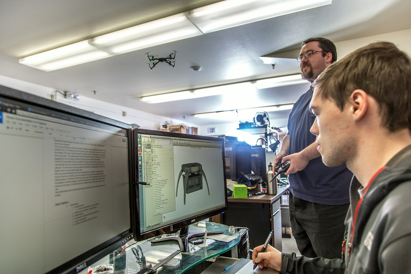 """Corey Upton, far right, a sophomore mechanical engineering major, studies the design of an unmanned aerial vehicle on his computer while Ph.D. candidate Steve Kibler flies such a craft around their south Fairbanks lab.  <div class=""""ss-paypal-button"""">Filename: AAR-13-4026-249.jpg</div><div class=""""ss-paypal-button-end""""></div>"""