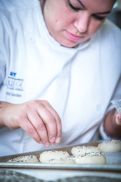 """Charlotte Gordon applies onion and garlic and poppyseed to mini-bagels served during lunch at CTC's culinary arts kitchen in the Hutchison Center.  <div class=""""ss-paypal-button"""">Filename: AAR-13-3811-129.jpg</div><div class=""""ss-paypal-button-end"""" style=""""""""></div>"""