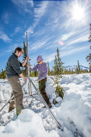 Daisy Huang, right, a research engineer for the Alaska Center for Energy and Power, works with ACEP intern Luke George to install a meteorological station on a hillside near the Black Rapids Lodge, about 150 miles southeast of Fairbanks. The station will record wind speed and direction, as well as temperatures at different altitudes.  Filename: AAR-13-3843-79.jpg