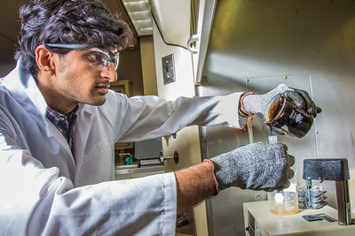 Graduate student Mukul Chavan pours a sample of heavy crude oil from the Kaparuk field on Alaska's North Slope. Chavan and other students in UAF's petroleum engineering program are using the samples to experiment with ways to recover more oil from existing fields.  Filename: AAR-13-3918-132.jpg