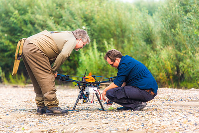 Tom Elmer, airspace manager for the Alaska Center for Unmanned Aircraft Systems Integration (ACUASI), and pilot Trevor Parcell inspect an unmanned aerial vehicle used to collect video of a popular stretch of the upper Chena River which serves as prime king salmon habitat.  Filename: AAR-15-4593-287.jpg